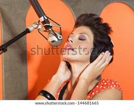 Closeup of a gorgeous female singer recording a track in a studio