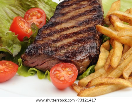 Closeup of a grilled steak with french fries, lettuce and cherry tomatoes