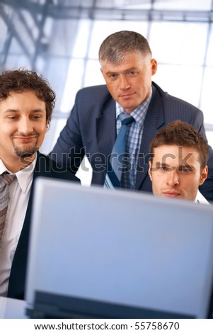 Closeup of a group of business people working on laptop with their manager at the office.