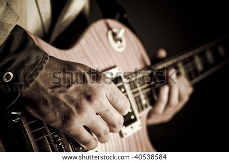 Closeup of a guitar with hand.