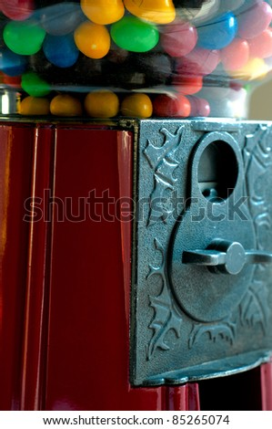 Closeup of a gumball machine with candy and penny slot
