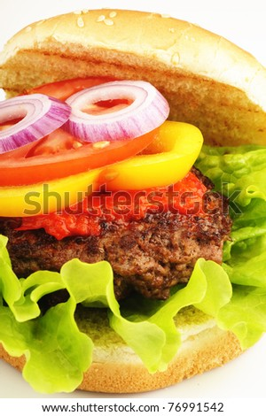 Closeup of a hamburger with bread, lettuce, sauce, pepper, tomato and onion