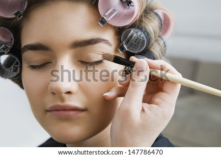 Closeup of a hand applying eyeshadow to female model