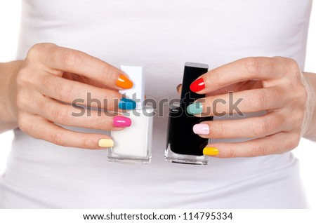 Closeup of a hand holding bottles with black and white nail polish