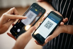 Closeup of a hand holding phone and scanning qr code. QR code payment and cash technology concept.