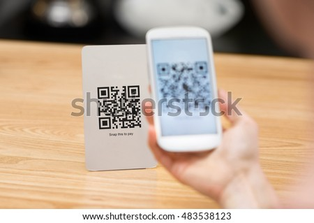 Closeup of a hand holding phone and scanning qr code. Woman hand paying with qr code. Close up of customer hand making payment through smart phone and scan code. #483538123