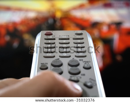 closeup of a hand  holding the remote control in front of the television, shallow DOF, conceptual image of the world under control