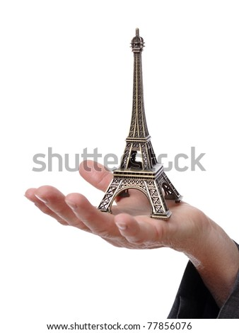 Closeup of a hand showing a tiny Eiffel Tower isolated on white background