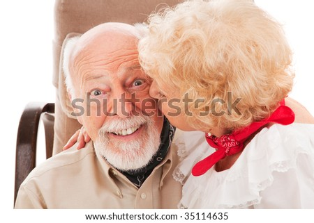 Closeup of a handsome senior man getting a kiss from his beautiful wife.