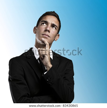 Closeup of a handsome young business man thinking against blue background