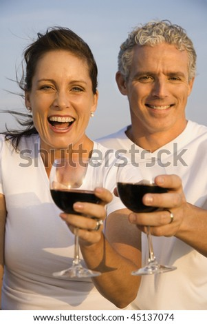 Closeup of a happy couple as they raise their glasses of red wine to the camera. Vertical shot.