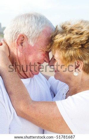 Closeup of a happy senior couple romancing on a beach