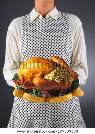 Closeup of a homemaker in an apron and oven mitts holding a platter with a roasted Thanksgiving turkey. Horizontal format over a light to dark background. Woman is unrecognizable.