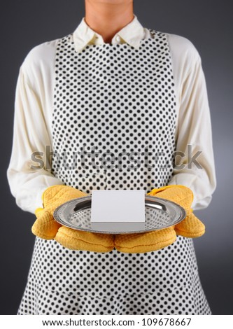 Closeup of a homemaker in an apron and oven mitts holding a tray with a plank place card. Horizontal format over a light to dark background. Woman is unrecognizable. Shallow depth of field.