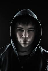 Closeup of a hooded teenager looking menacing