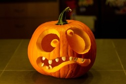 Closeup of a jack-o-lantern isolated on the kitchen counter. Funny halloween pumpkin face.