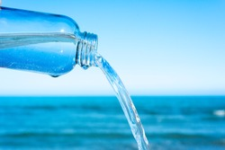 closeup of a jet of water flowing out of a glass reusable bottle, with the ocean in the background