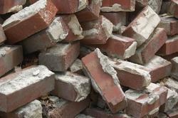 closeup of a jumble pile of reclaimed bricks with cement mortar attached