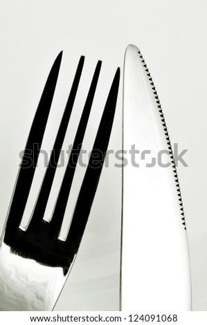 closeup of a knife and a fork on a white tablecloth