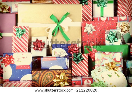 Closeup of a large stack of wrapped Christmas presents of varying sizes and shapes  #211220020