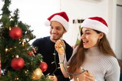 Closeup of a Latin couple putting on some Christmas decorations at home and having some fun together