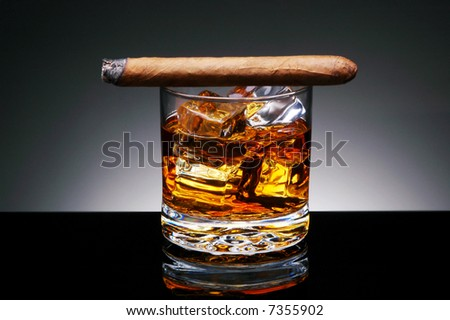 Closeup of a Lit Cigar resting on top of a  glass of whiskey and ice cubes on a black reflective surface with a light to dark gray background. Horizontal format