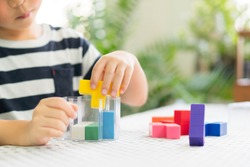 Closeup of a little boy's hands playing colorful block puzzles, problem solving, cognitive skill, concentration/emotional intelligence, Learn through play, Early education, Child development concept.
