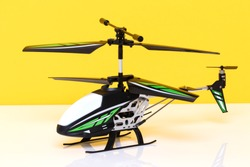 Closeup of a little remote controlled toy helicopter on a bright table against yellow background. Macro photograph of RC helicopter.