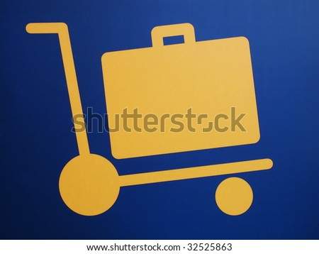 Closeup of a luggage cart airport sign, yellow symbol on dark blue background