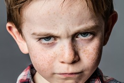 closeup of a mad little kid with furious blue eyes and freckles for attitude and childhood rebellion, contrast effects