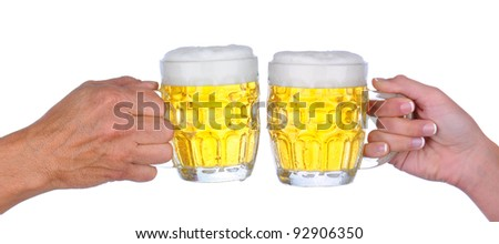 Closeup of a male and female hand a woman hand holding a beer mug  with a frothy head about to clink glasses, over a white background.