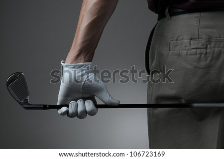 Closeup of a male golfer holding a six iron behind his body. Man has a Golf Glove on his hand. Horizontal format over a light to dark gray background. - stock photo