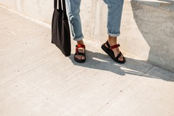 Closeup of a male legs in trendy red leather sandals in blue vintage jeans with a black fabric bag. Young man in fashionable clothes is standing on the asphalt on a sunny day. Casual summer look.