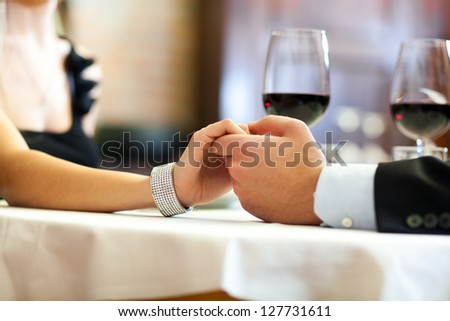 Closeup of a man holding his girlfriend's hand at the restaurant