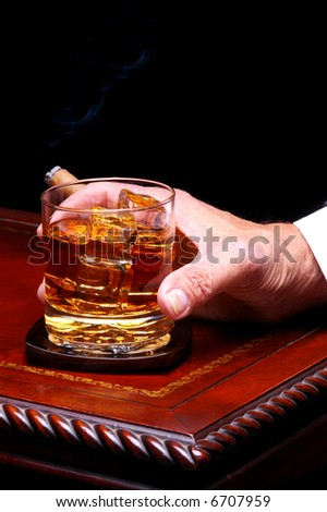 Closeup of a man holding on to his glass of whiskey on the rocks and a cigar on an elegant wood table. Vertical format with a black background.