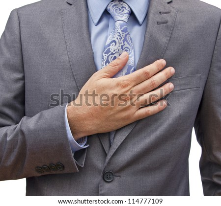 closeup of a man in a suit with his hand over his heart