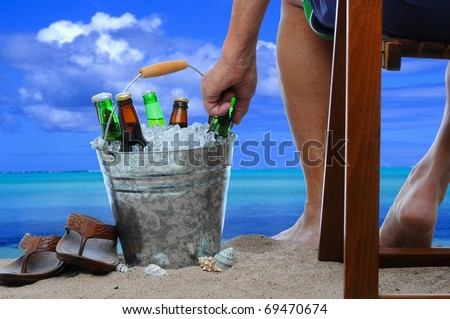 Closeup of a man on vacation sitting in a wooden chair at the beach reaching into a bucket filled with ice and beer bottles.