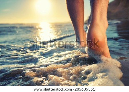 Closeup of a man's bare feet walking at a beach at sunset, with a wave's edge foaming gently beneath them, toned colors #285605351