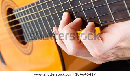 Closeup of a man's fingers playing the guitar