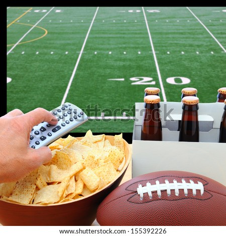 Closeup of a man\'s hand holding a TV remote with a bowl of chips and a six pack of beer with a football field on the television screen in the background. Square Format.