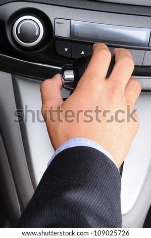 Closeup of a man's hand on the gear shifter of his car. Vertical Format. Man and car are unrecognizable.