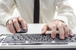 Closeup of a man using computer. His shirt and tie in background.