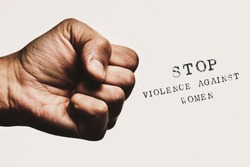 closeup of a man with his fist threateningly closed and the text stop violence against women against an off-white background