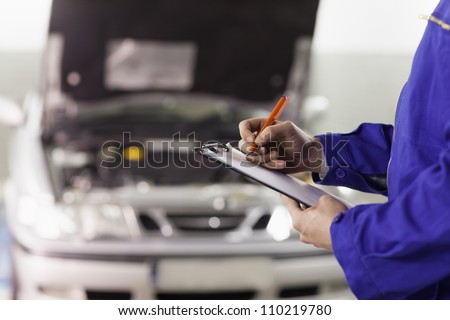 Closeup of a man writing on a clipboard in a garage