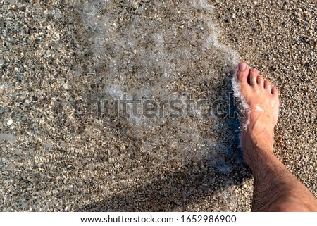 Closeup of a mans bare foot at the beach in the clean water