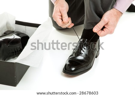 Closeup of a mans hands tying the laces on a new pair of shoes. - stock photo