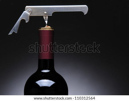 Closeup of a metal waiters corkscrew in a wine bottle. Horizontal format over a light to dark gray background.