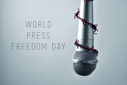 closeup of a microphone encircled by a red barbed wire and the text world press freedom day on a gradient gray background