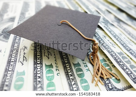 closeup of a mini graduation cap on cash