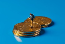 closeup of a miniature adventurer man observing a map standing on a pile of bitcoins on a blue background, depicting the adventurous and risky nature of investing in this virtual currency